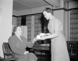 [Red Cross volunteer serving refreshments to a woman at a blood donor clinic]