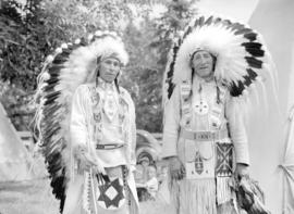 [Two Stoney Indians in costume, posing at Calgary Stampede parade]