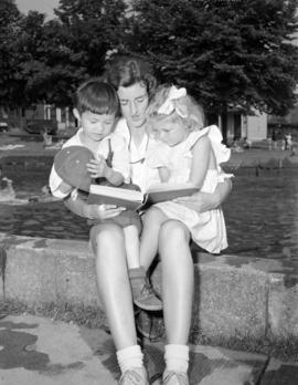 [Playground leader reading to two young children at a park]