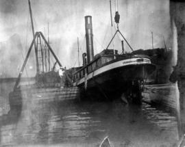 [Unidentified man overseeing ship being raised from or lowered into water]