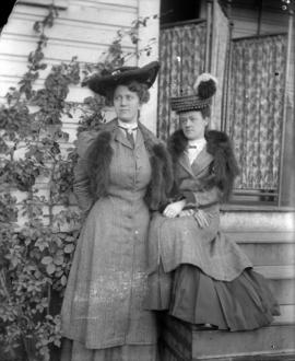 [Two women in hats and furs on front steps]