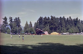Children playing in field in front of red and white canopy