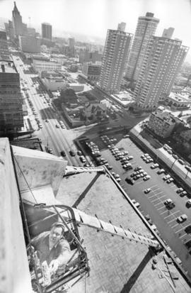 """Working 230 feet above Georgia Street, John Kurath applies finishing touches to cement work..."
