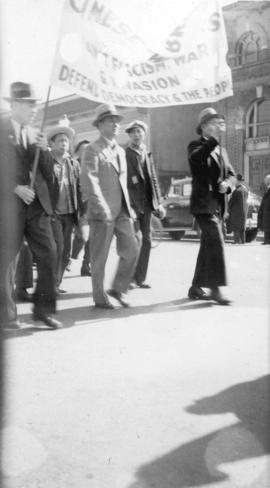 A group of Chinese men carrying a banner against fascism, war and invasion, in a parade