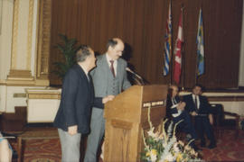 Unidentified man and Mike Harcourt at podium in Hotel Vancouver Grand Ballroom