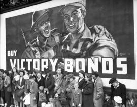 People at a parade standing in front of a Victory Bonds billboard