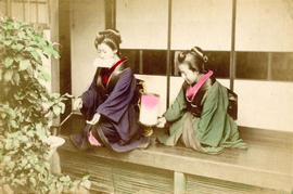 [Two women in formal Japanese dress kneeling on a deck]