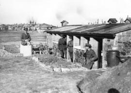 [Royal Engineer Officers in front of cottages built from materials from ruined Salonica villages]