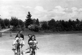 Children on tricycles, West Memorial, [looking east]