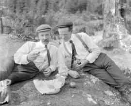 [Two men eating a picnic lunch]