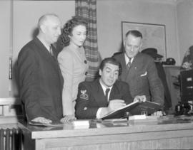 [Group watching a naval officer sign the guestbook at the Seamen's Club]