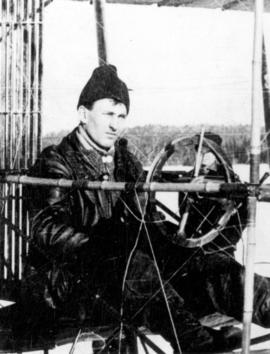 "James A.D. McCurdy [at the controls of the ""Silver Dart"" Pusher Biplane]"