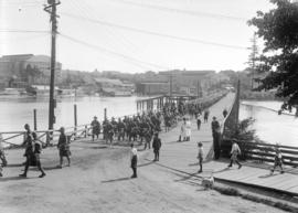 72nd Seaforths [marching over bridge to Stanley Park - taken from park - shows Vancouver arena an...