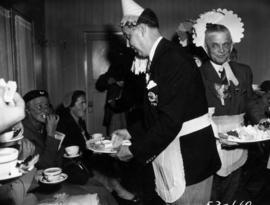 P.N.E. Vice-President T.R. Fyfe in maid costume serving snacks at tea party