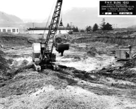 Excavation of site for P.N.E. B.C. building with Livestock building and sheep barn in background