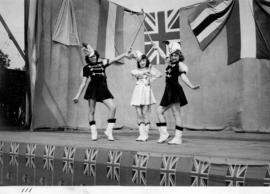 Three baton twirlers on outdoor stage
