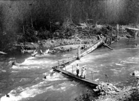 [A man and woman crossing a floating bridge]