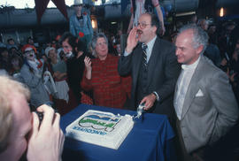 Pat Carney, Mike Harcourt and unidentified cutting cake for Vancouver's 99th birthday celebration