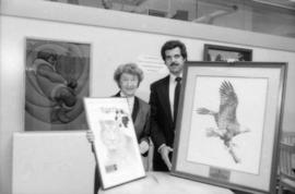 May Brown and unidentified man holding prints from the Centennial gift program