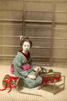 [Studio portrait of a woman in formal Japanese dress kneeling on the floor with drums]