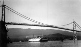 View of the Lion's Gate Bridge with a ship passing below