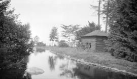 [Log structure beside stream in Stanley Park]