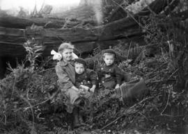 Three unidentified children seated on a blanket in brush