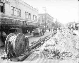 [Men laying power cables under Smithe Street]