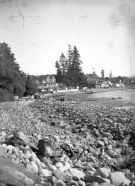 [English Bay beach, showing rocky beach area and houses]