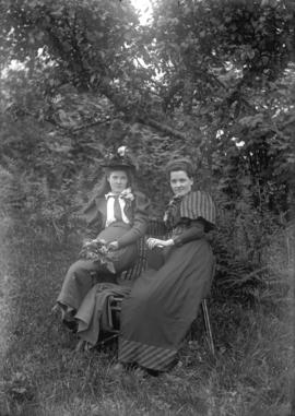 [Miss McFarland and unidentified girl seated on bench in wooded area]