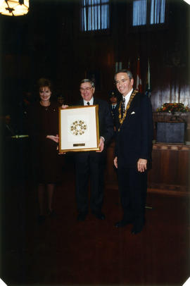 Diana Fowler LeBlanc, Roméo LeBlanc and Mayor Philip Owen pose with print by Susan Point