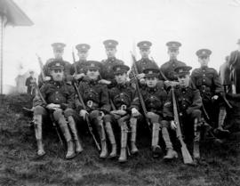 Group of ten high school army cadets seated on a hill