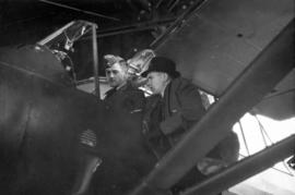 [R.C.A.F. Squadron Leader Jack Gledhill and another man beside an airplane]