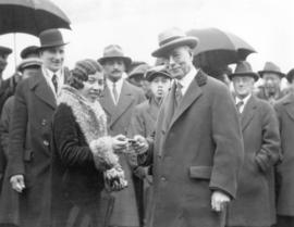 [Mayor L.D. Taylor exchanging object with young woman, possibly an actress, in front of a crowd g...