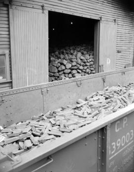 [Railway car full of metal bars passing by a coal shed at Evans, Coleman, and Evans, Ltd.]