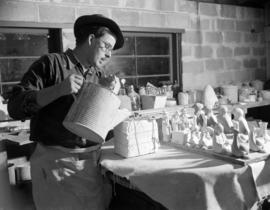 [Man making figurines using a ceramic mould]