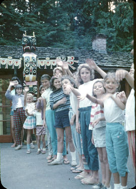 Children lined up in front of Totem pole at Camp Capilano