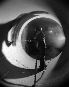 [Man painting the inside of a boiler at Vancouver Iron Works Ltd.]