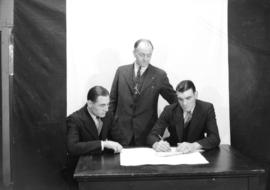 Jack Allen [watches as] G. Wallace and Tommy Bland sign a contract
