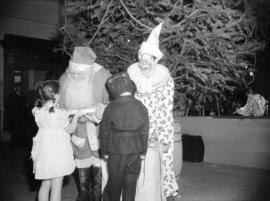 [Children receiving gifts from Santa Claus and a clown at a Christmas party]