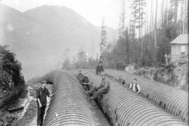[Group of men posing with completed wooden penstocks for Buntzen Lake Power Plant number one]