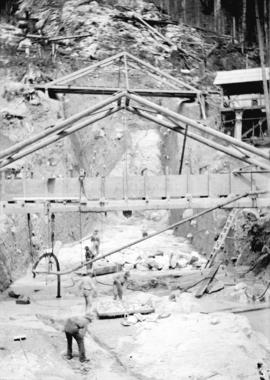 [Men working under scaffolding in partially excavated area for Buntzen Lake Power Plant number one]