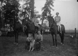 Women on horses and men with a dog sitting in front