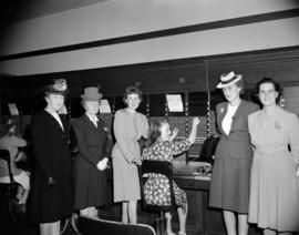 [Group portrait of five women standing around a B.C. Telephone operator]