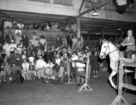 Boy riding horse as crowd watches in Livestock building