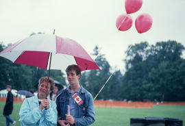 Man and woman under umbrella during the Centennial Commission's Canada Day celebrations