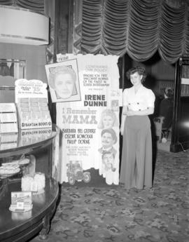 "[Theatre usher standing by a poster for the movie ""I Remember Mama"" in the lobby of the..."