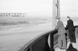 [Men on ship looking at the Lions Gate Bridge under construction]