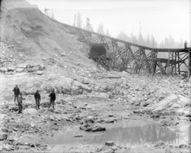 [Men standing in partially excavated area of Coquitlam Dam construction site]