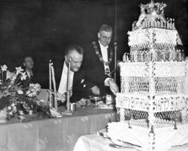[Premier T.D. Pattullo cutting his birthday cake]